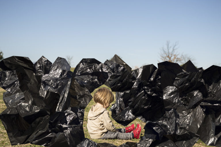small child sititng on a landscape surrounded by black pieces of plastic
